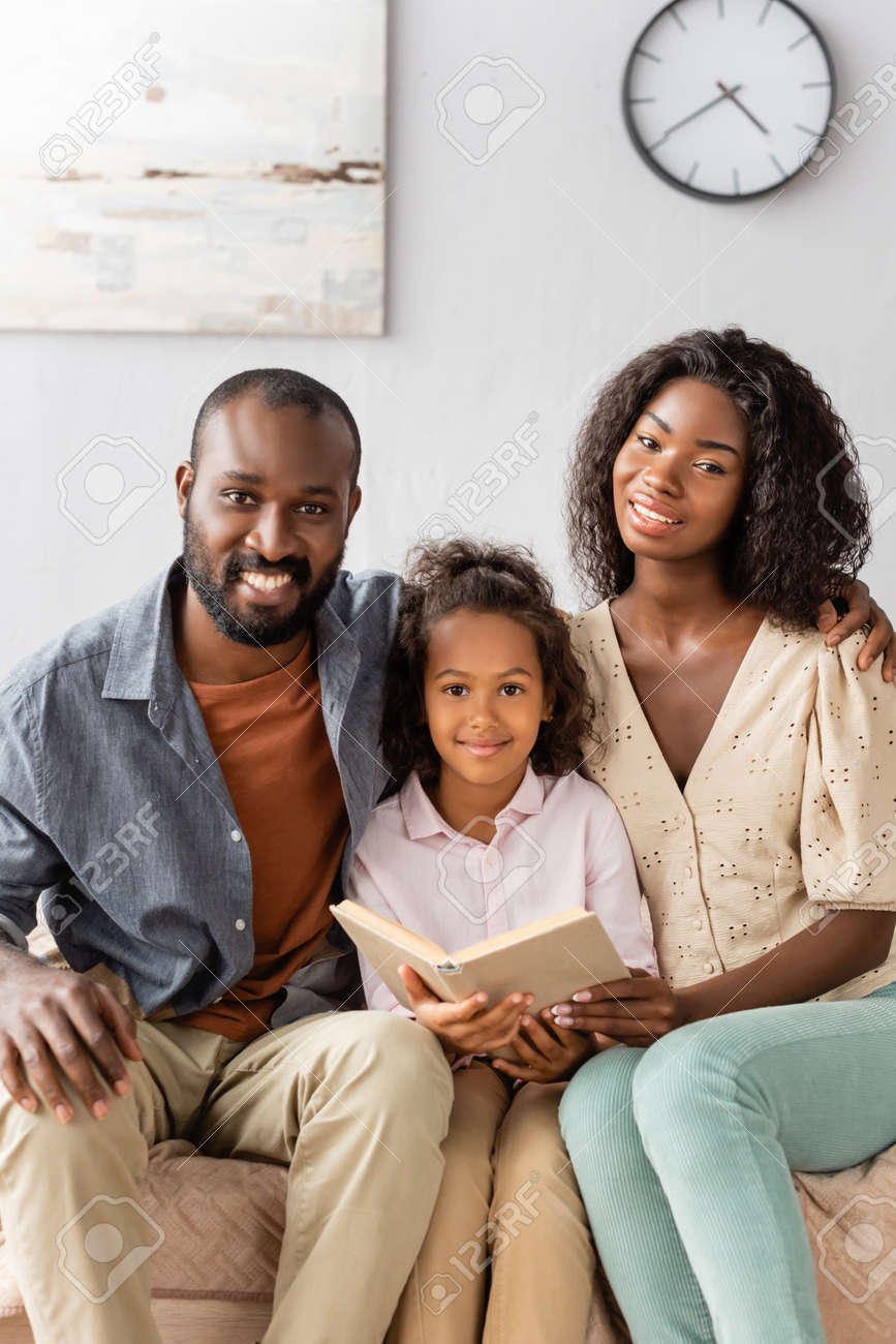 young african american parents and child with book looking at camera while sitting at home - 154299993