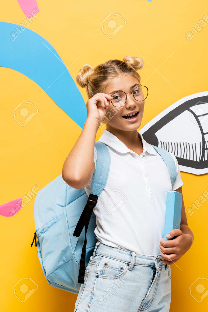 excited schoolchild touching eyeglasses and looking at camera while holding book near colorful elements and paper pencil on yellow - 155382057