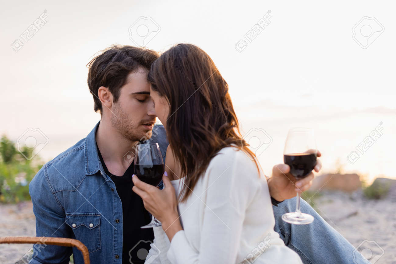 Young couple with glasses of wine kissing on beach at sunset - 156592425