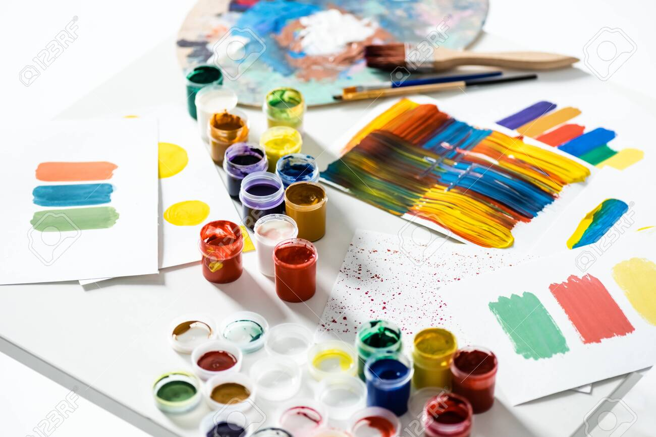 gouache paints, paintbrushes and abstract colorful brushstrokes on paper on white background - 157540407