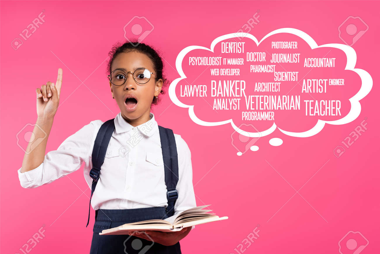 shocked african american schoolgirl with book showing idea gesture near thought bubble with greeting lettering on pink - 158768154