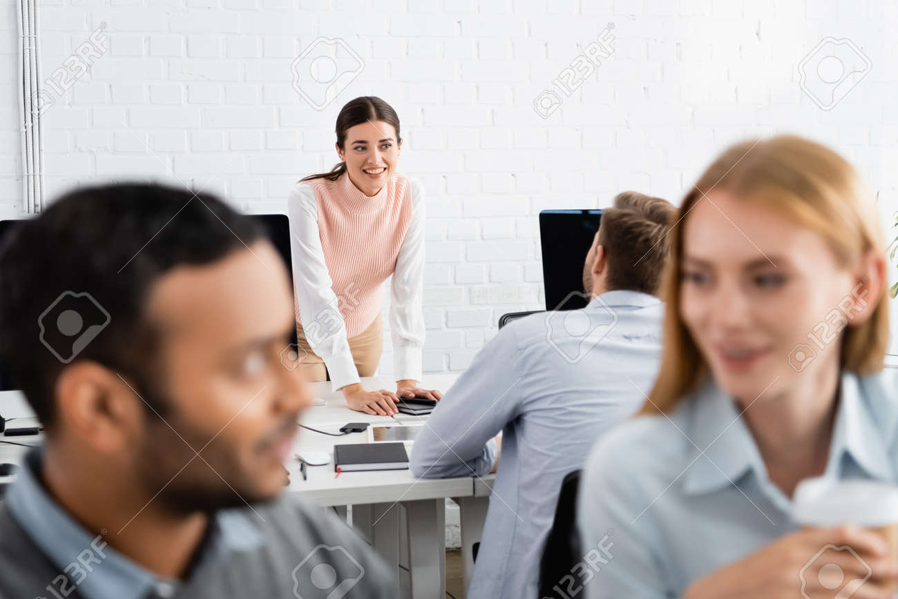 Smiling businesswoman looking at colleague near devices in office - 158496803