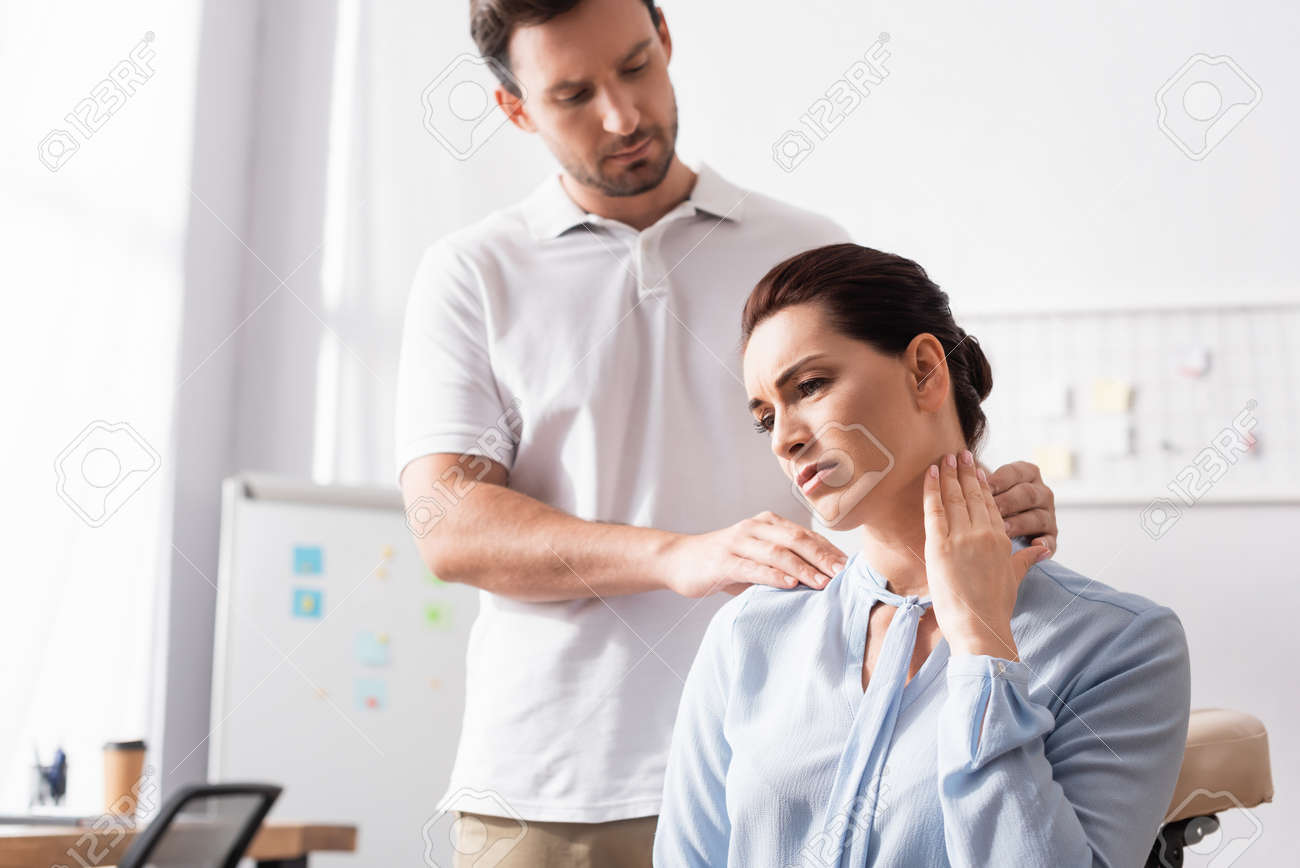 Massage therapist massaging painful neck of businesswoman with blurred office on background - 159130835