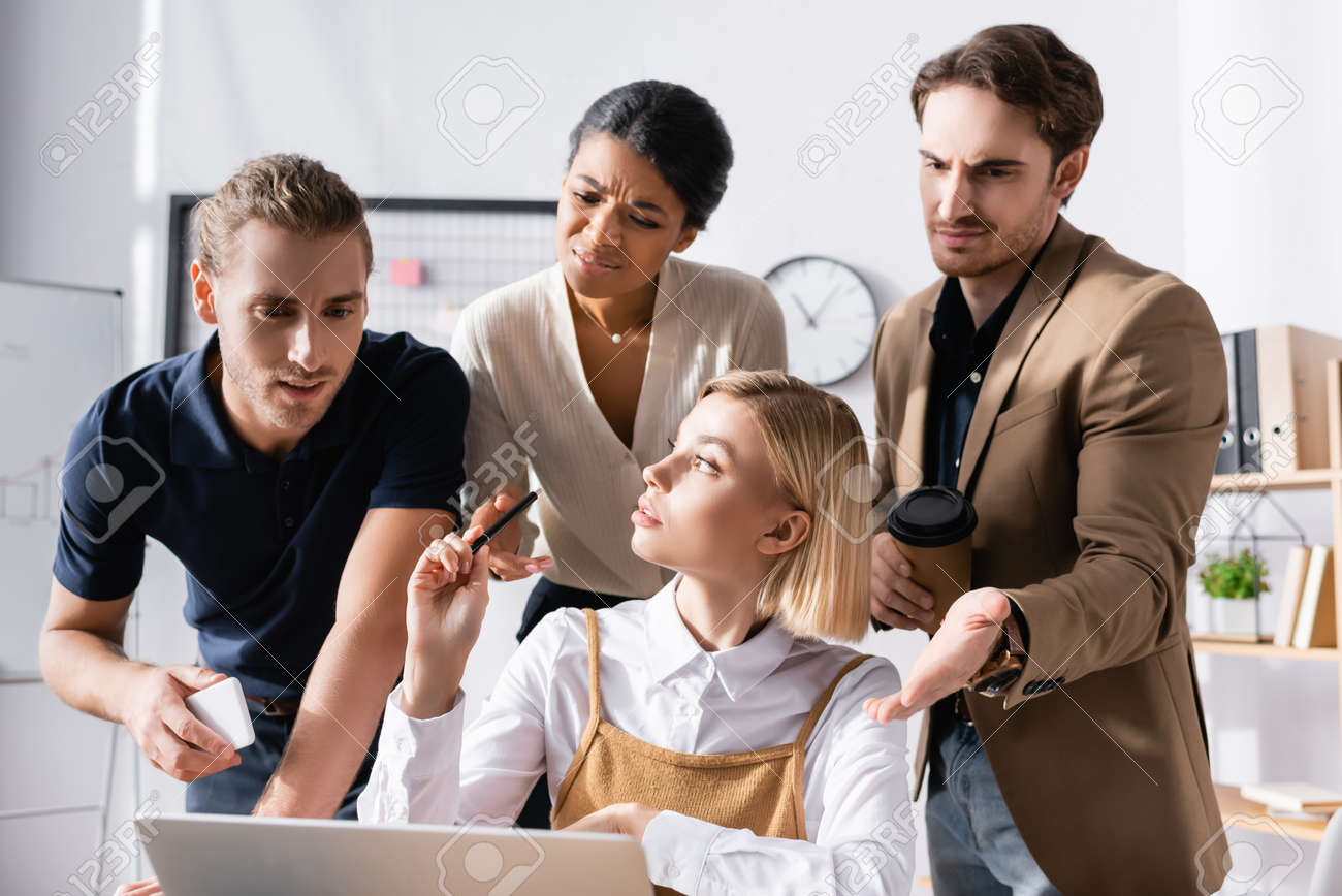 Blonde woman looking away while sitting at table with skeptical, multicultural office workers standing behind and looking at laptop at workplace - 159250777