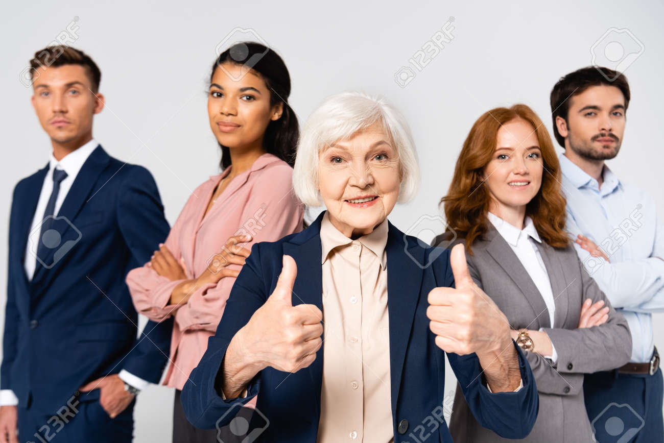 Smiling businesswoman showing like near multicultural businesspeople on blurred background isolated on gray - 159250409