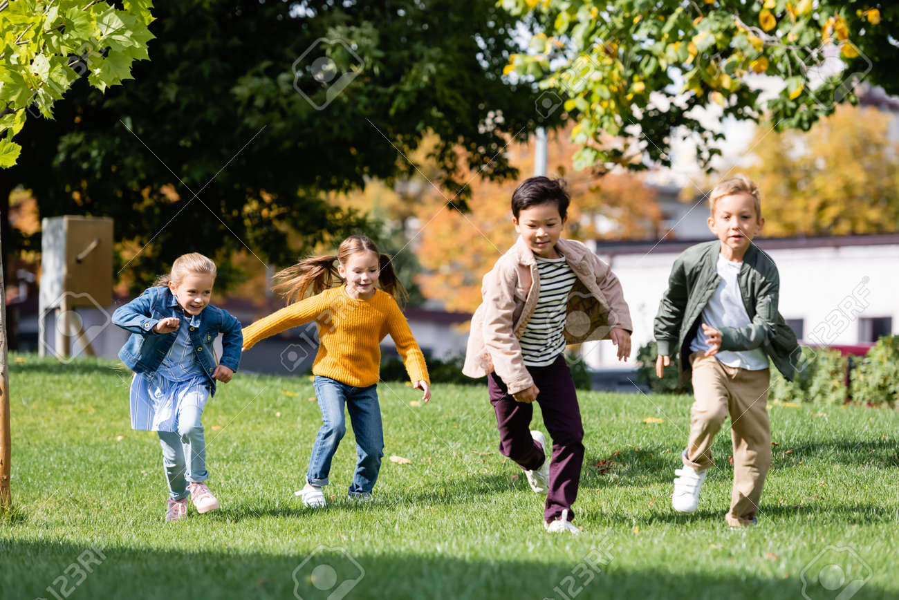 Smiling multiethnic children running on grass in park - 159464313