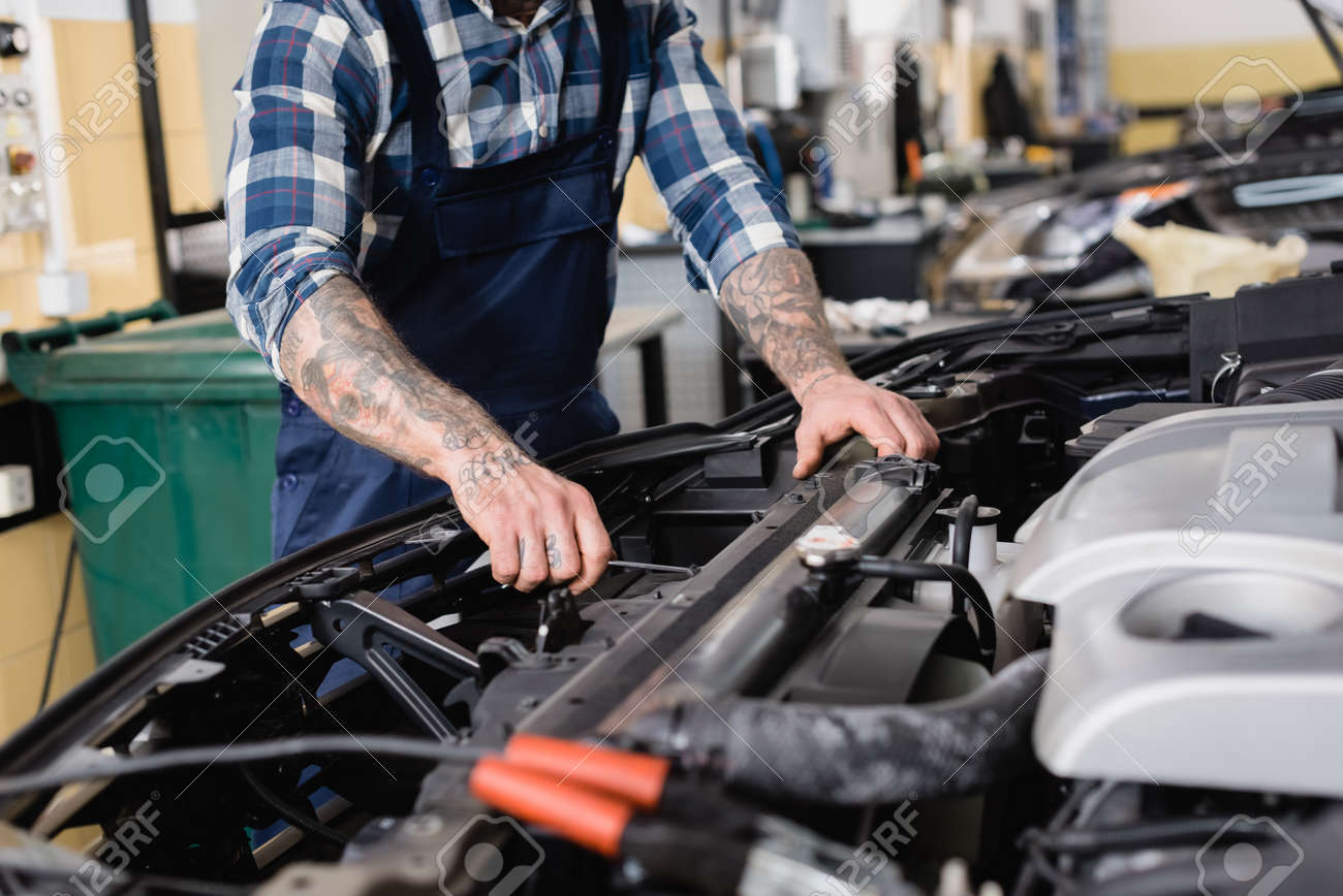cropped view of mechanic checking car engine compartment in workshop on blurred foreground - 159530333