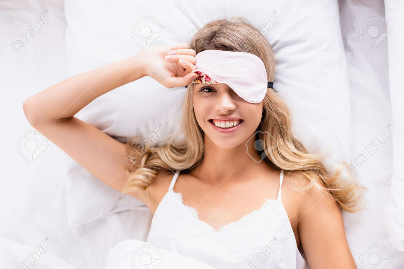 Top view of young woman in blindfold smiling at camera on bed - 159629047