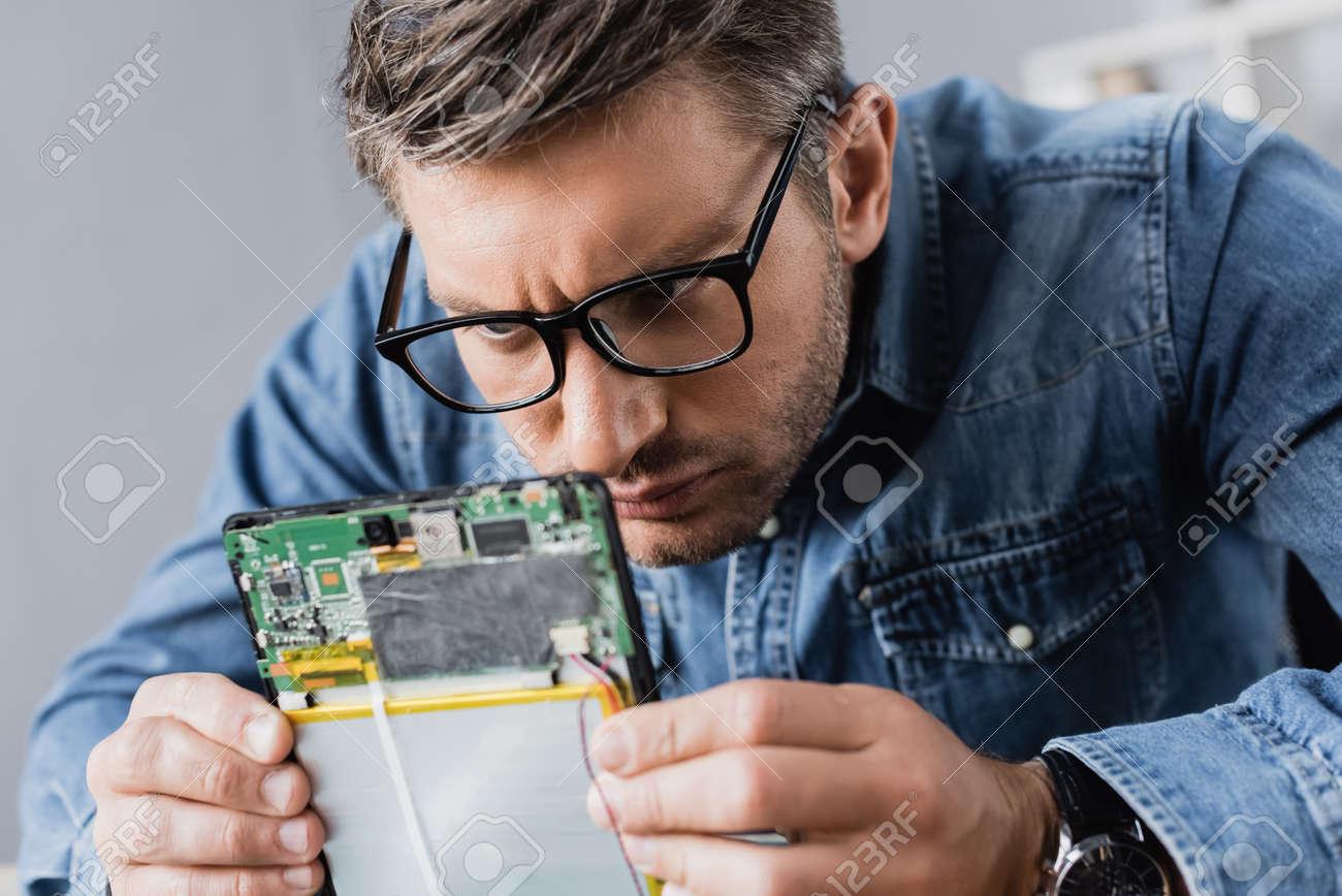 Focused repairman in eyeglasses looking at part of broken digital tablet - 159901957