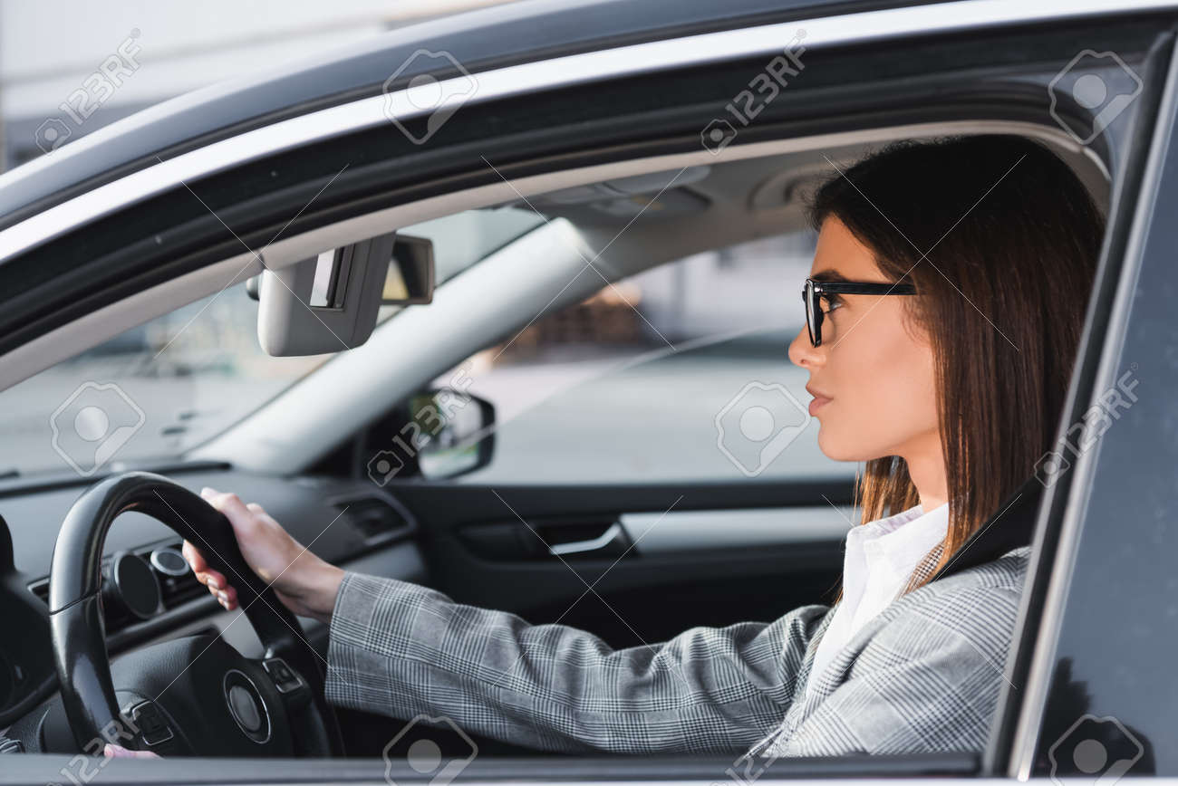 side view of businesswoman in eyeglasses looking ahead while driving car - 159979797