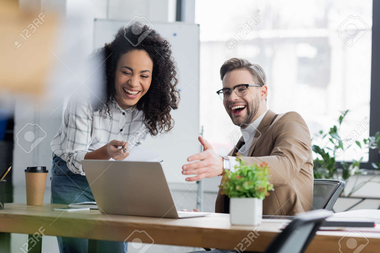 Cheerful multiethnic business people using laptop in office - 166709602