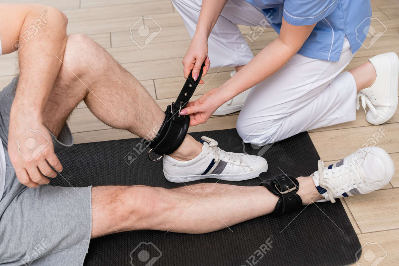 cropped view of trainer fastening leather belt on leg of man in rehabilitation center - 166814297