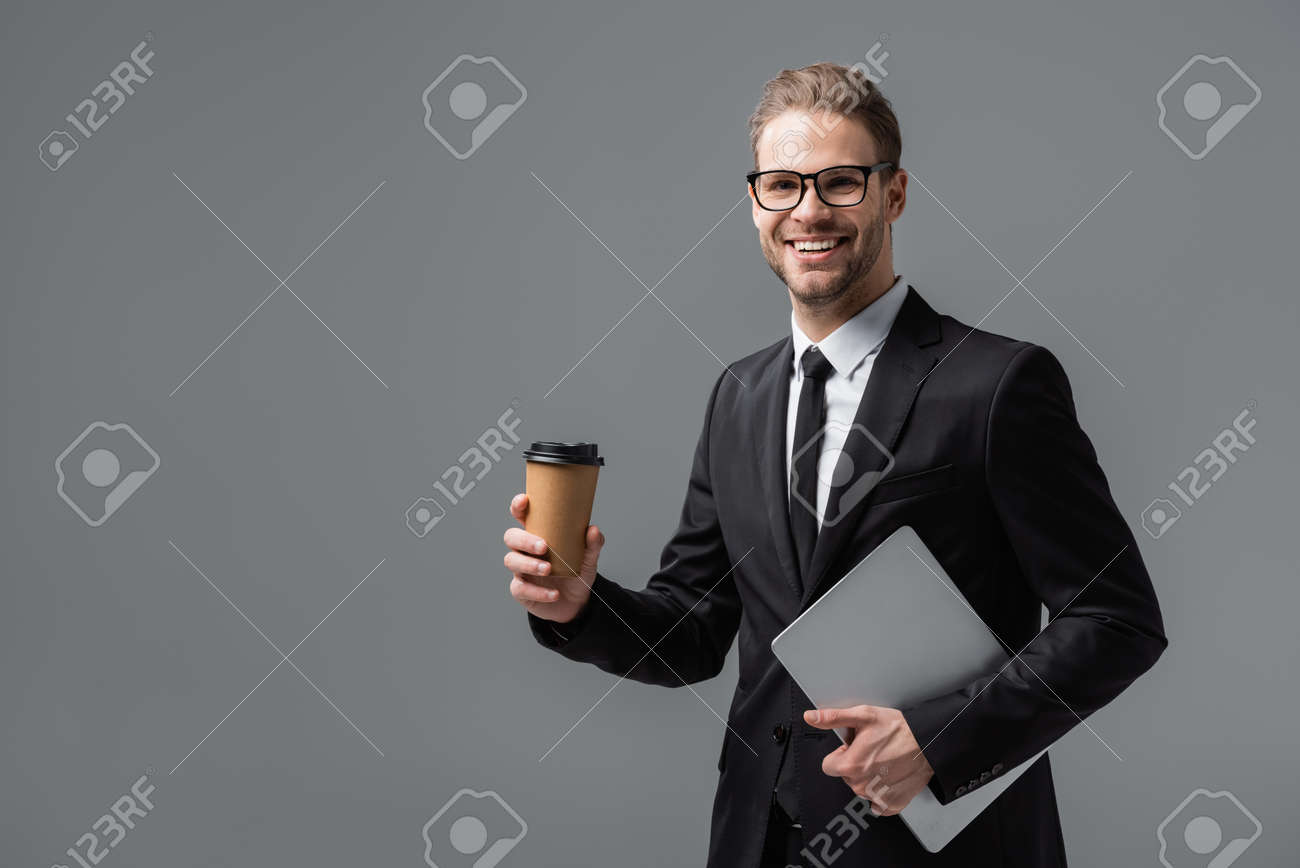 happy businessman with takeaway drink and laptop smiling at camera isolated on gray - 167016466