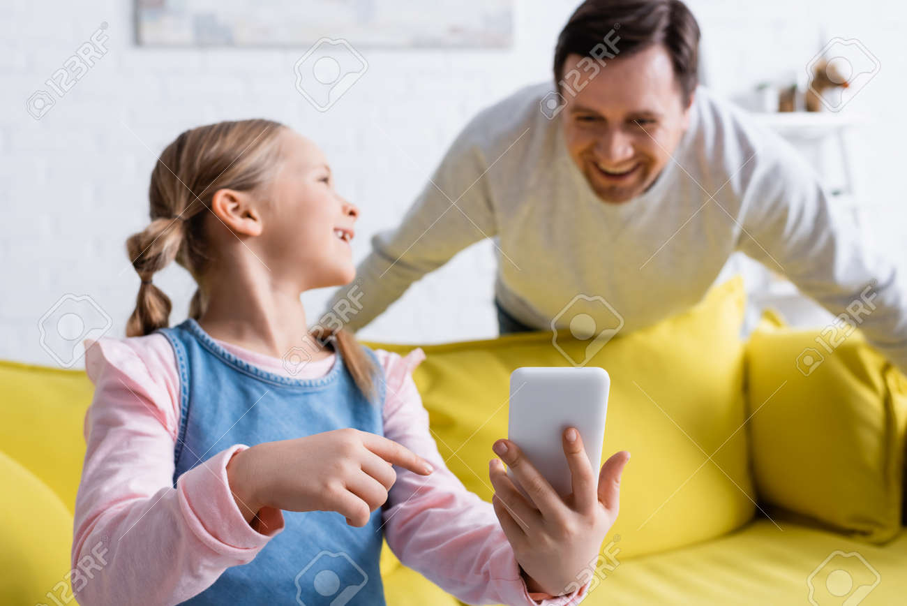 smiling girl pointing at mobile phone near father laughing on blurred background - 167592285