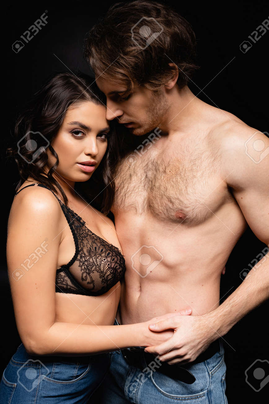 woman in lace bra holding hands with shirtless man isolated on black - 167765300