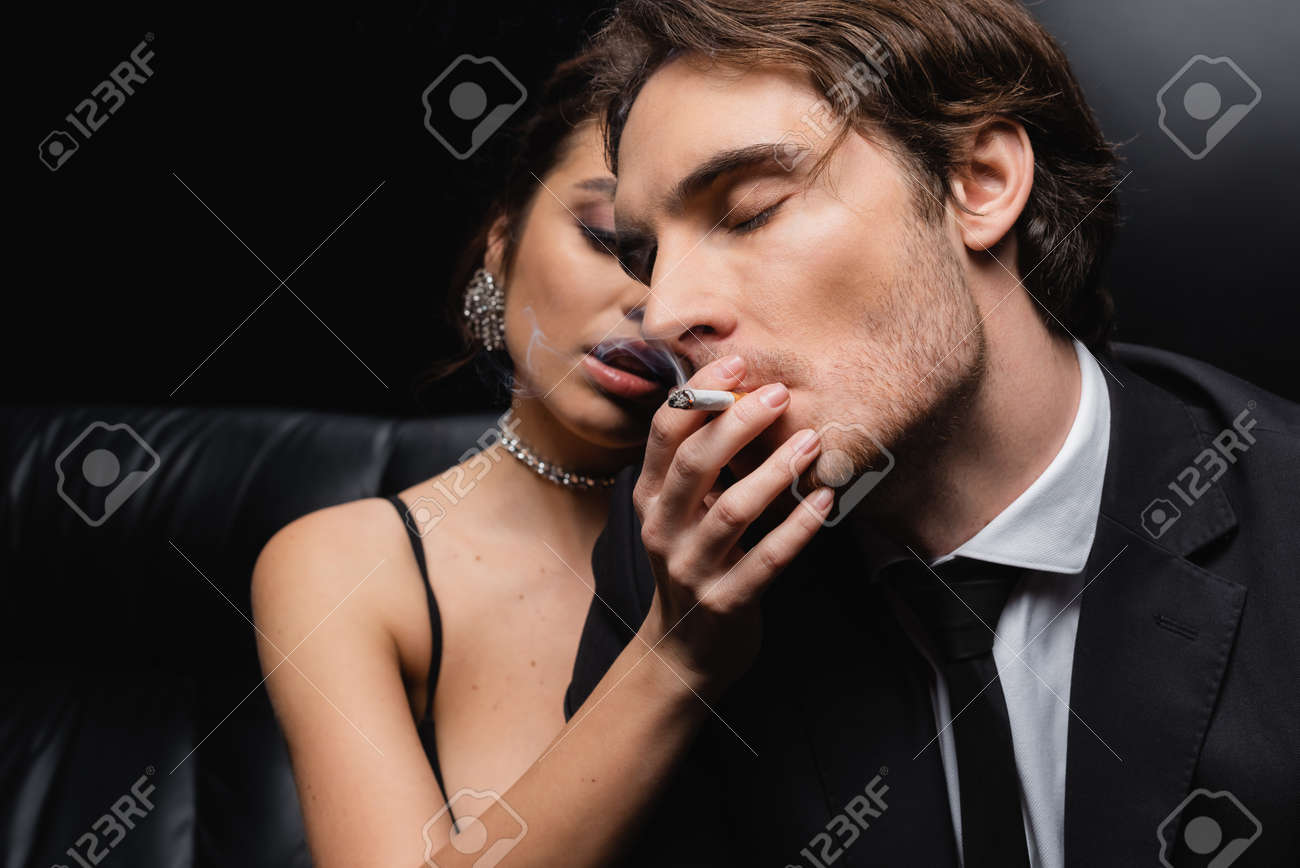 blurred seductive woman holding cigarette near man in suit on black - 167768965