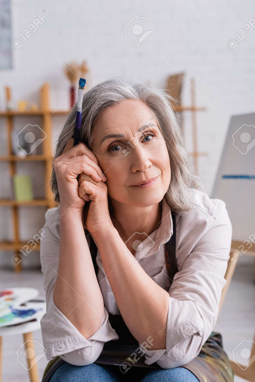pleased middle aged painter with gray hair holding paintbrush - 167949517