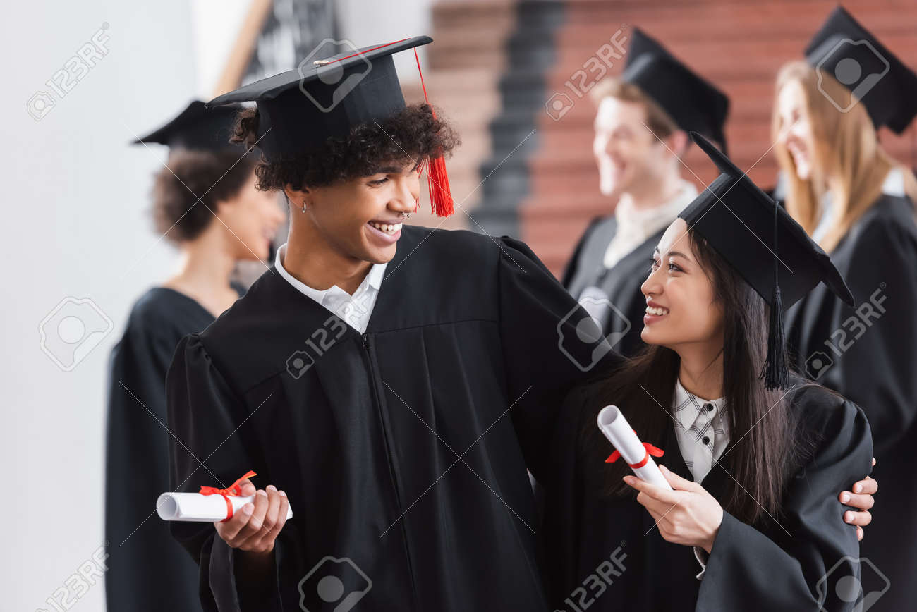 African american graduate hugging asian friend with diploma - 168003158