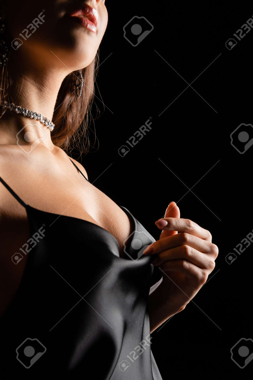 cropped view of sensual woman in silk dress touching with hand isolated on black - 169341574