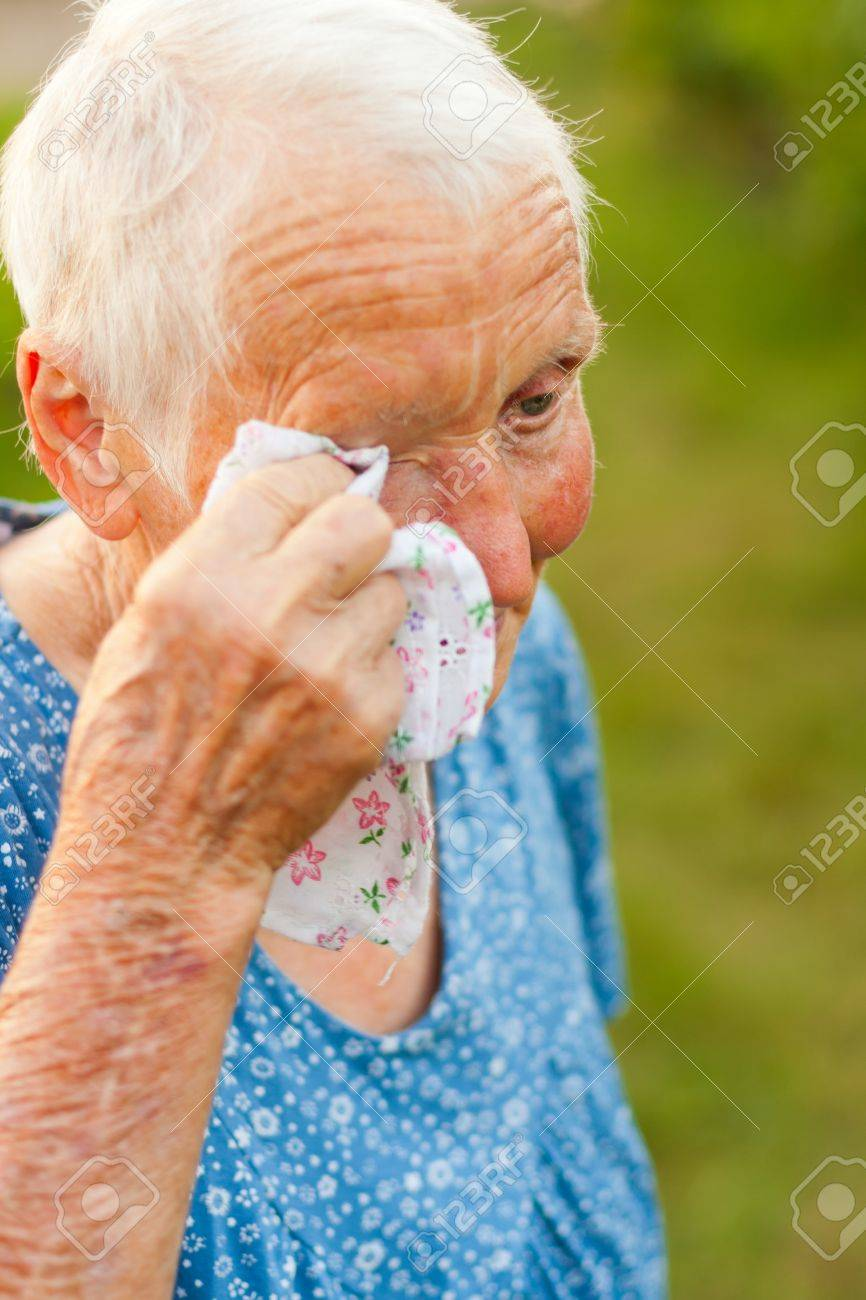 Old lady wiping her tears with a handkerchief. - 17751526