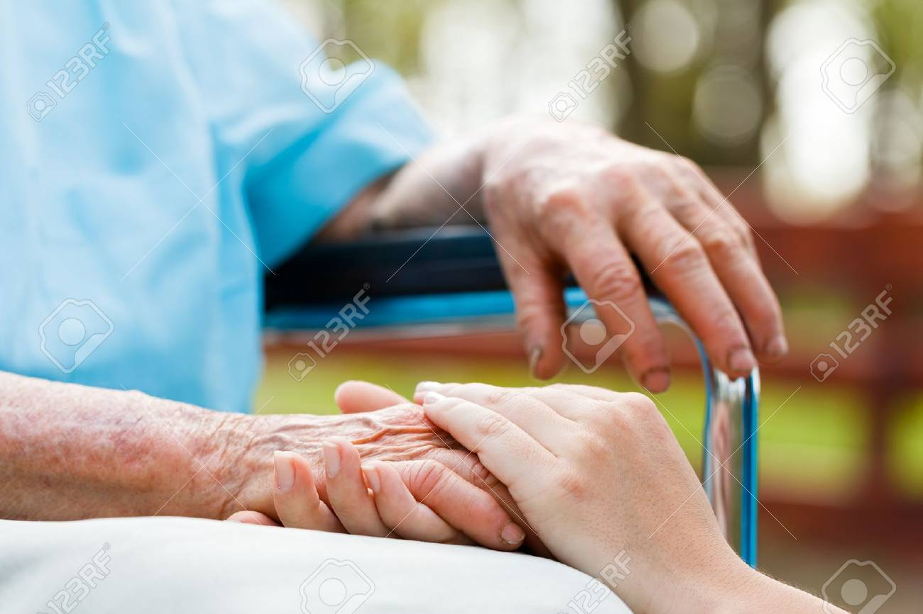 Doctor holding elderly patient 's hand in a wheelchair. Stock Photo - 31202455