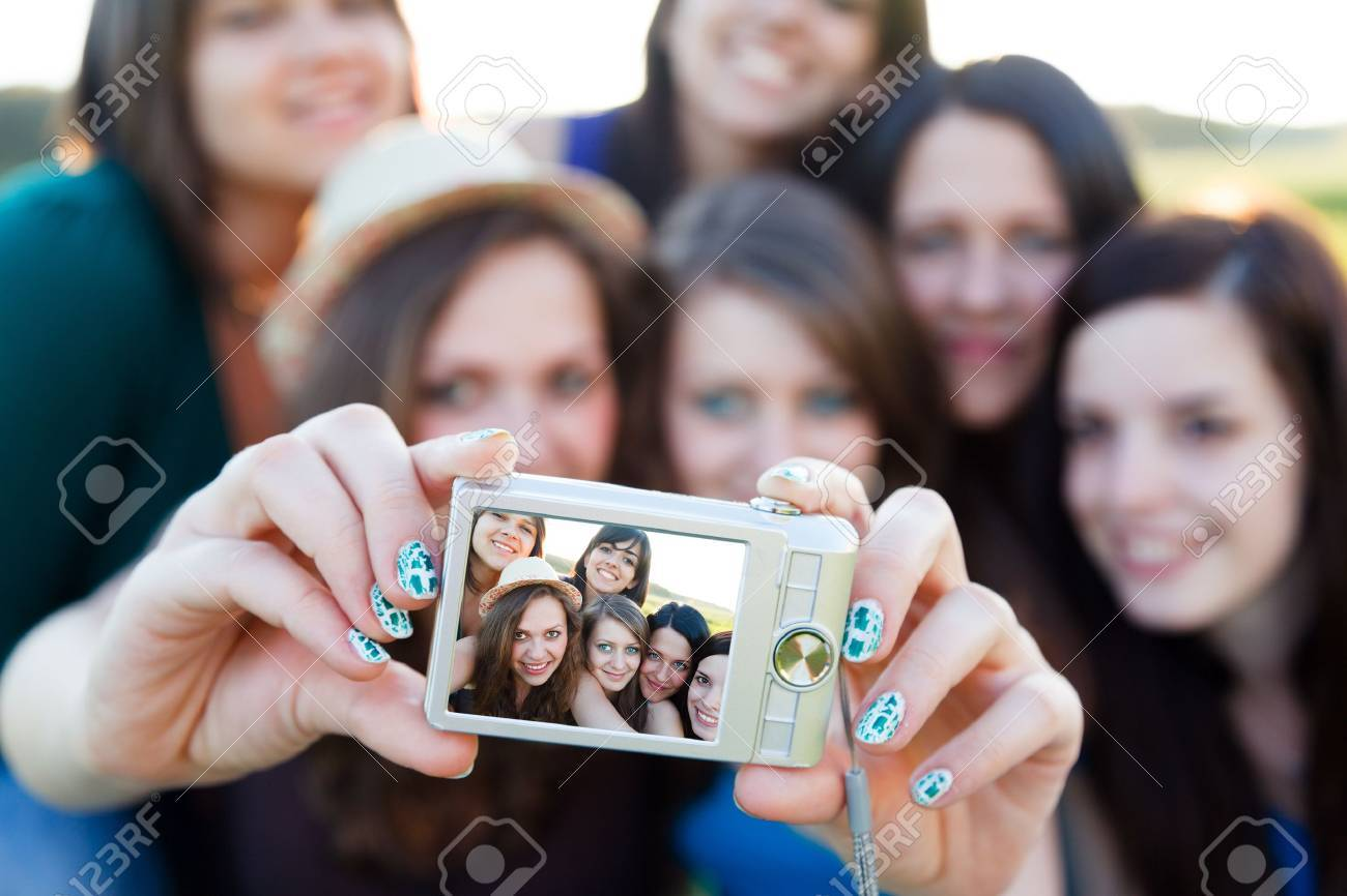 Pretty girl taking picture with her girlfriends - selfpic series Stock Photo - 20797849