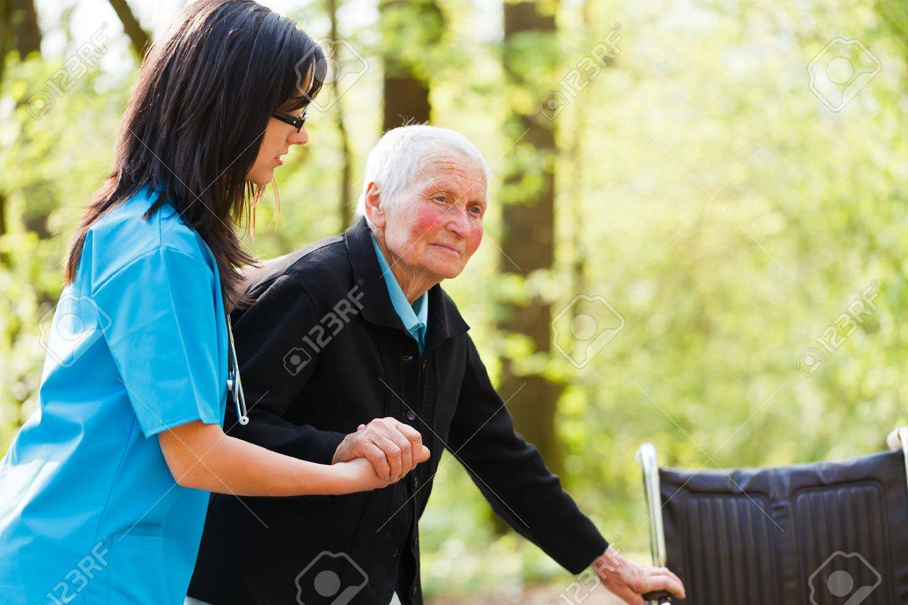 Caring nurse or doctor helping elderly patient to sit down on her wheelchair. Stock Photo - 21829770