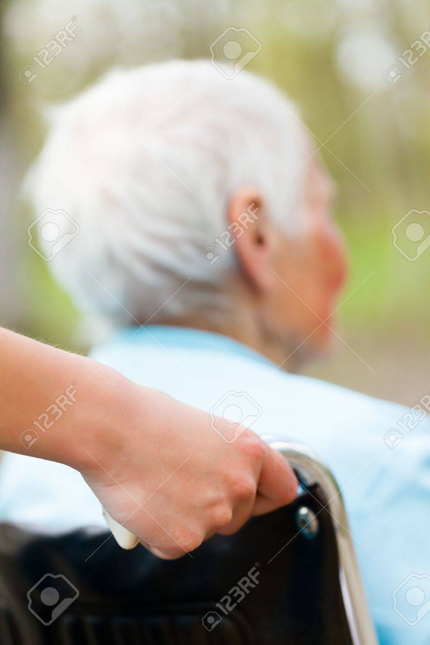 Nurse pushing wheelchair outdoors with senior patient. Stock Photo - 21829538