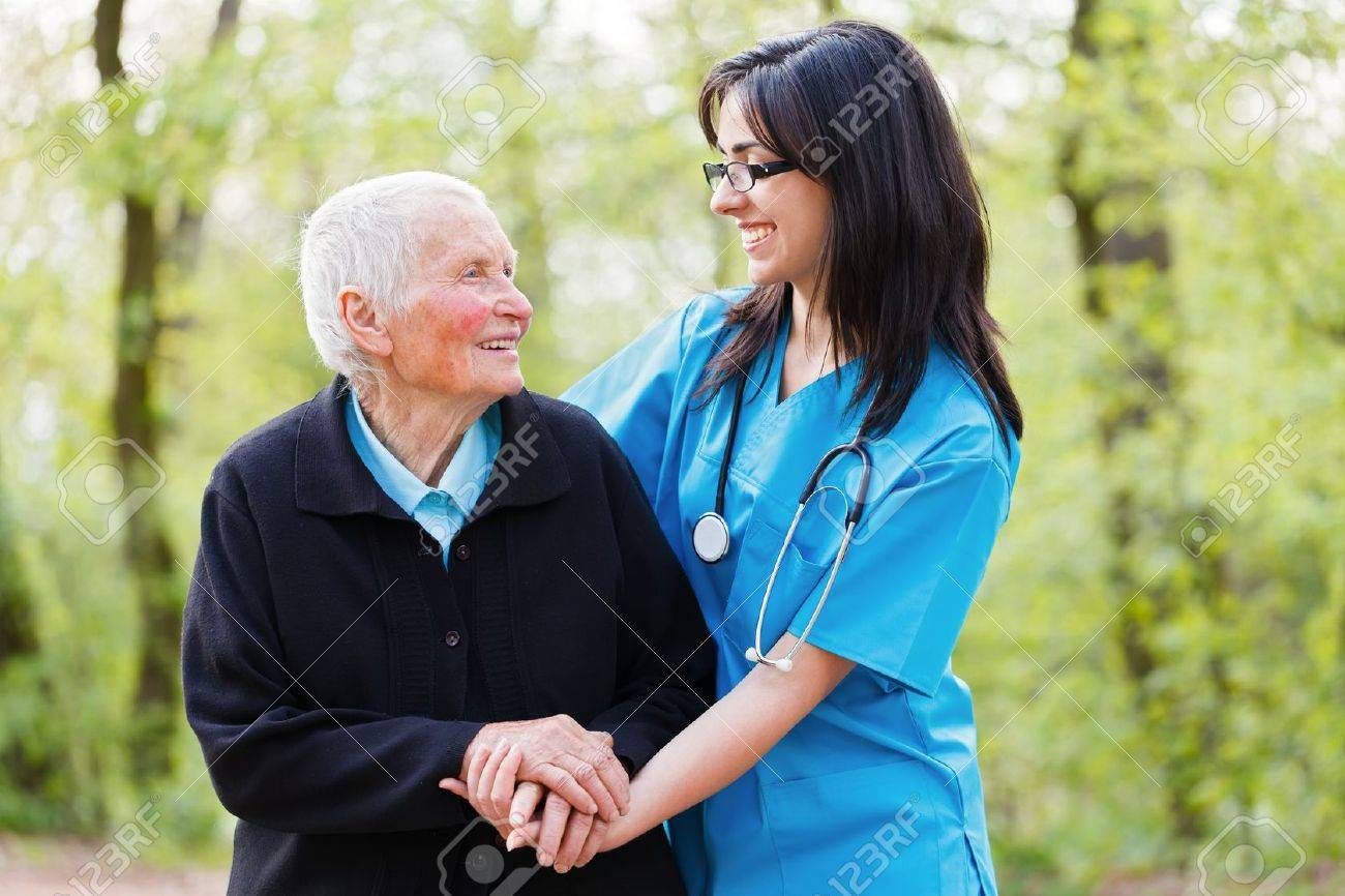 Portrait of caring nurse and happy senior lady while  holding hands. Stock Photo - 21829824