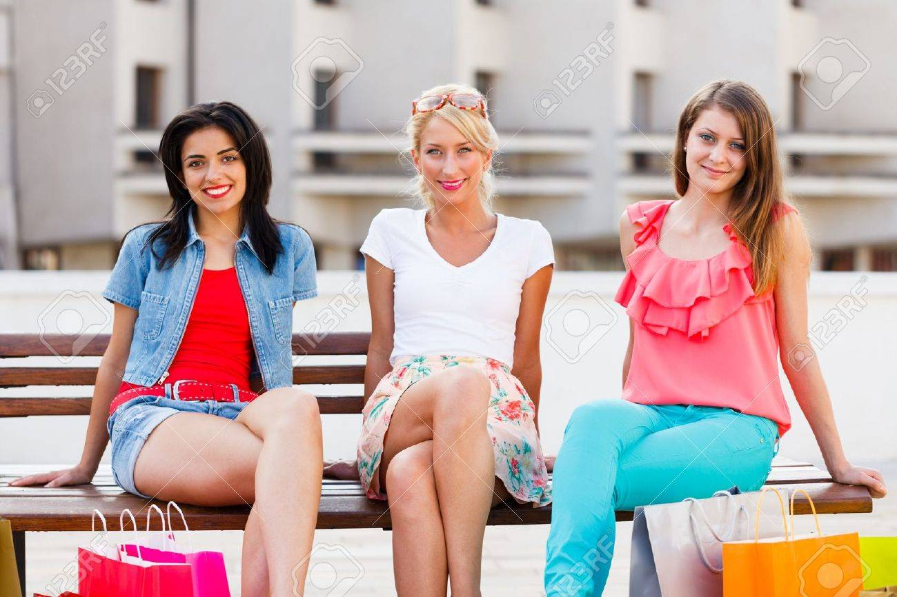 Three beautiful women in the city sitting on a bench and smiling . Stock Photo - 21829859