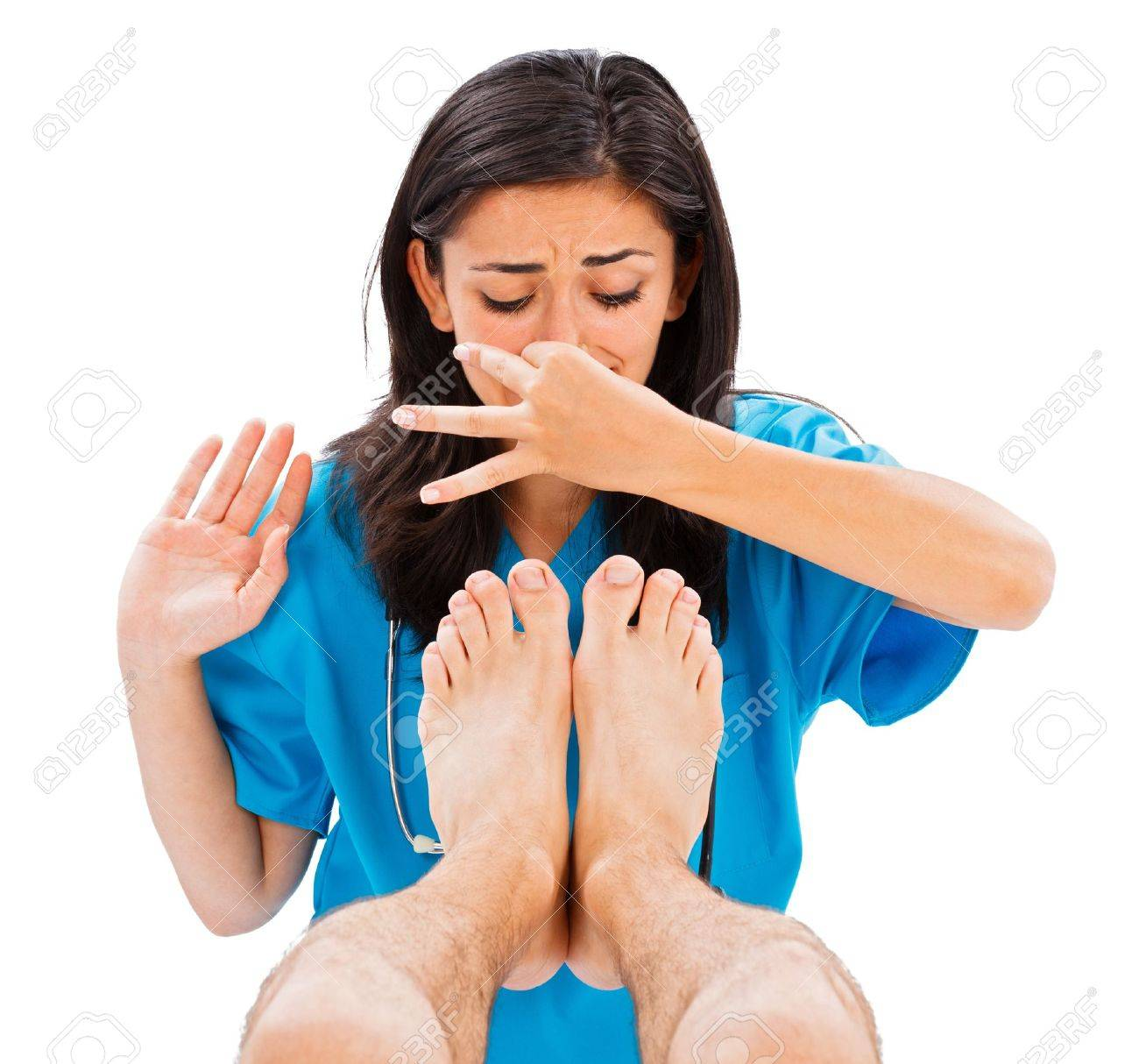 Female doctor holding her nose not to smell the man's stinky feet - isolated image. Stock Photo - 21829608