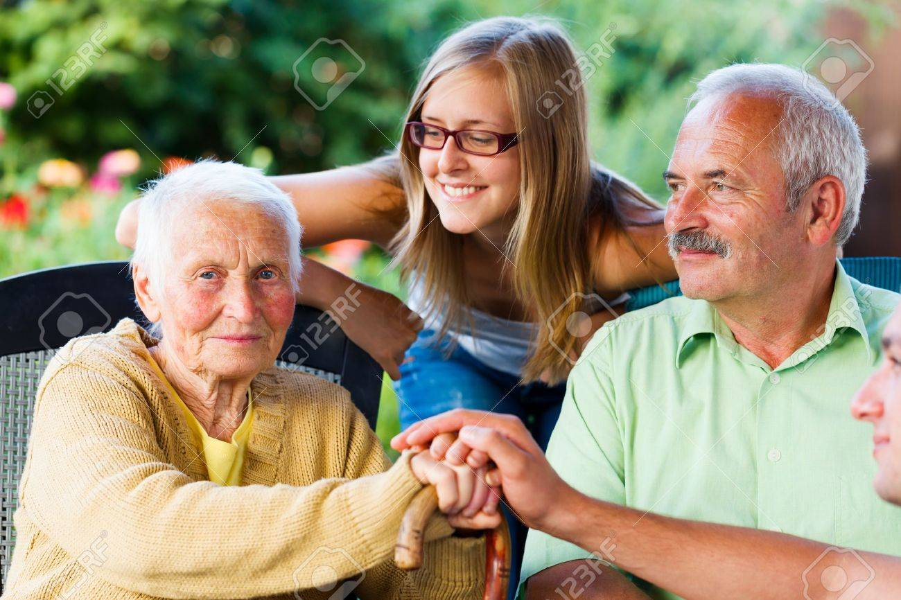 Elderly woman welcoming her family - son and granddaughter in the garden of the nursing home. Stock Photo - 21830066