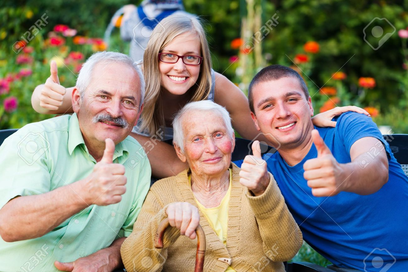 Happy, contented family showing thumbsup for the quality of the residential care of grandmother. Stock Photo - 21829781