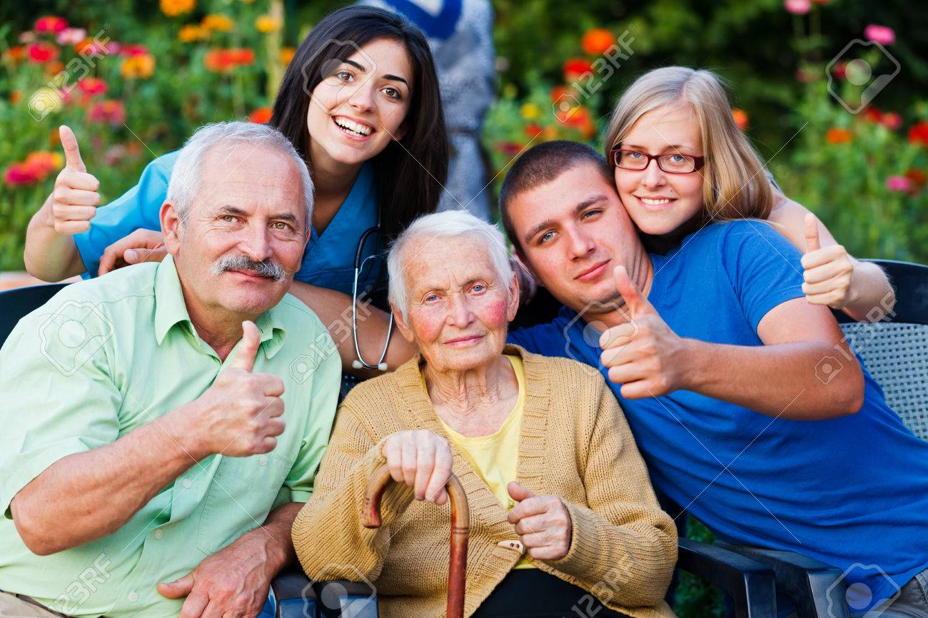 Happy group of people - family and doctor - showing thumbsup for the high quality services in the residential home. Stock Photo - 31324708