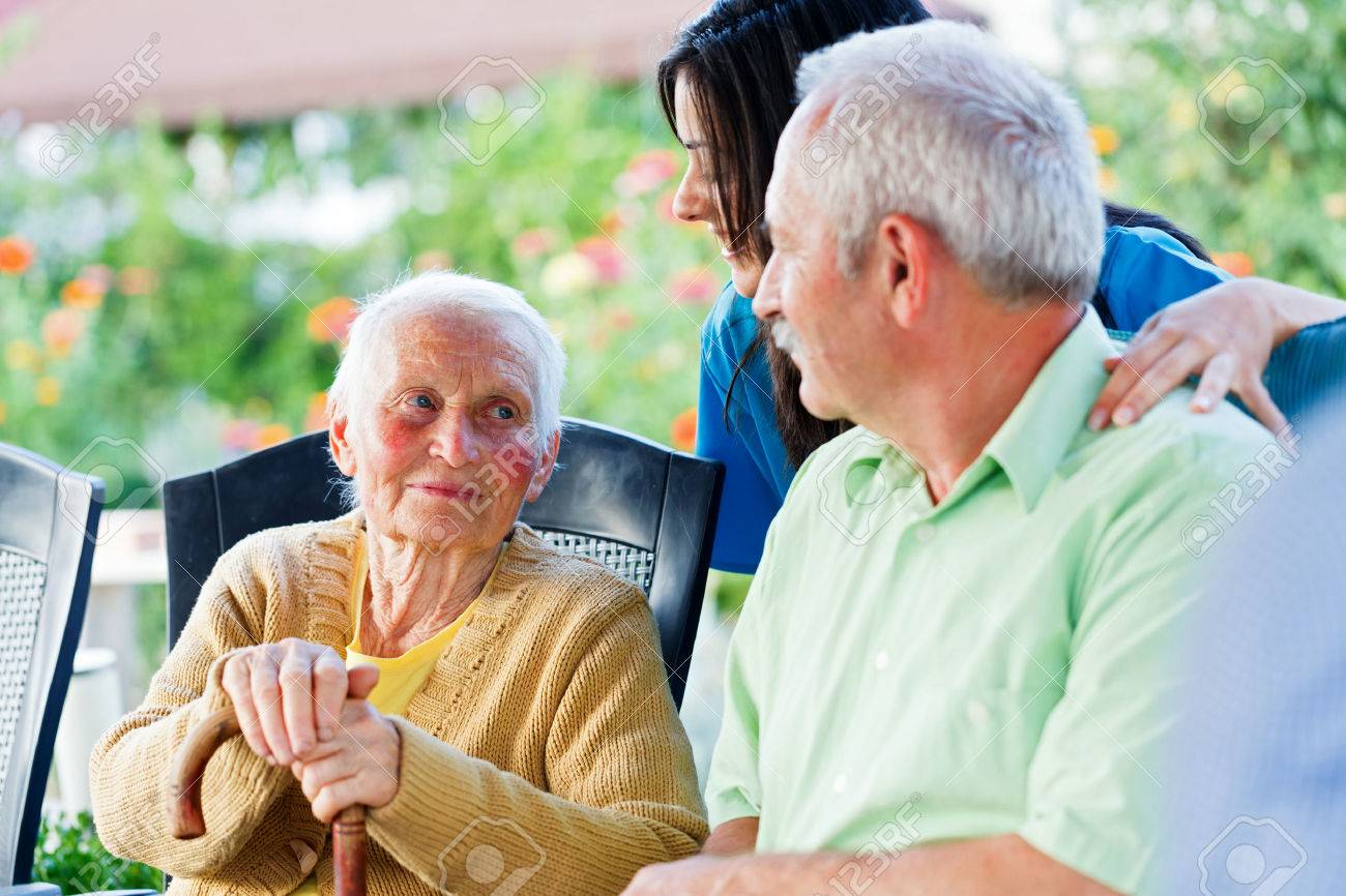 Elderly woman looking to the carer and her son, the visitor. Stock Photo - 31324767