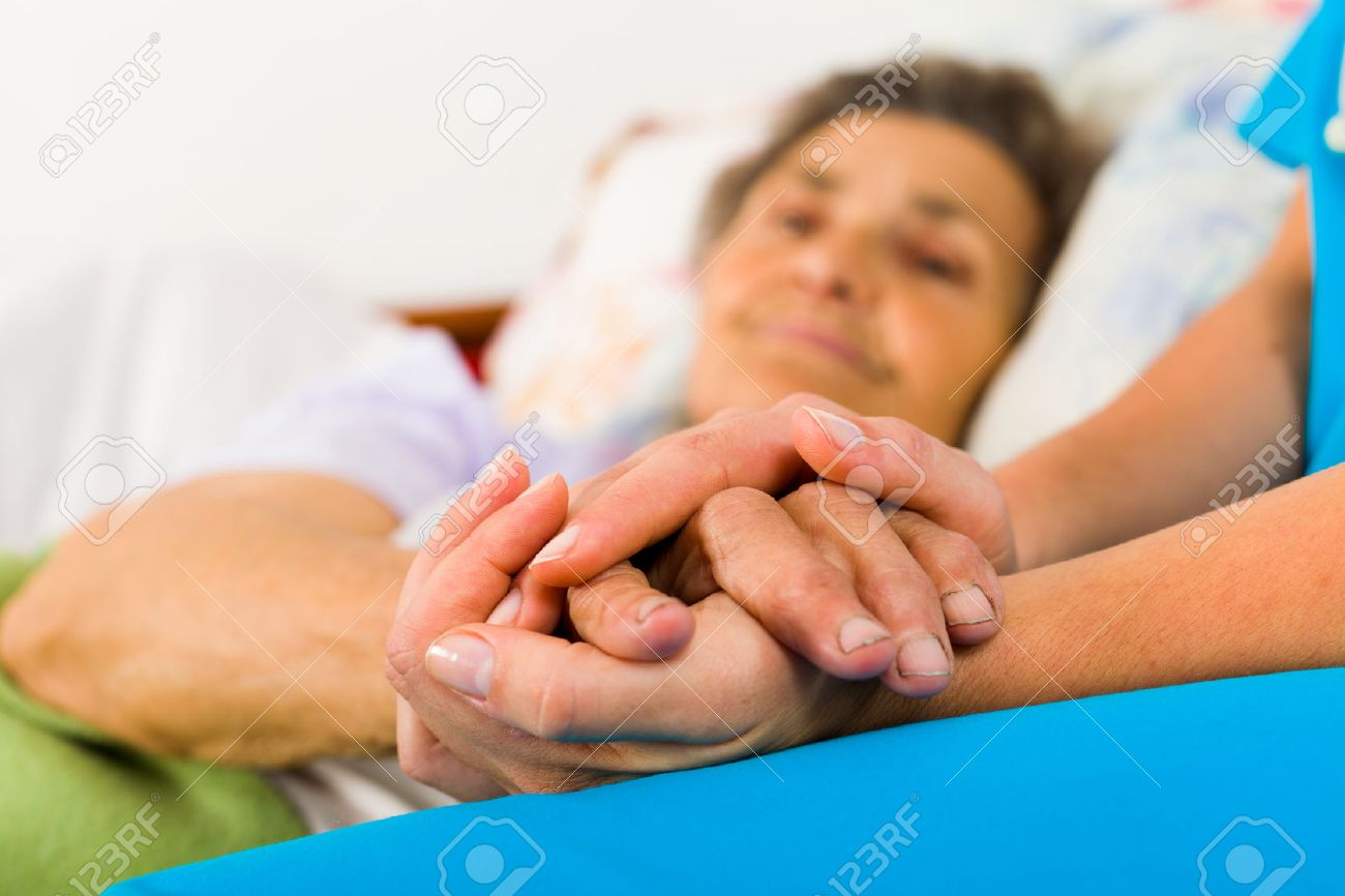 Caring nurse holding kind elderly lady's hands in bed. - 55422020