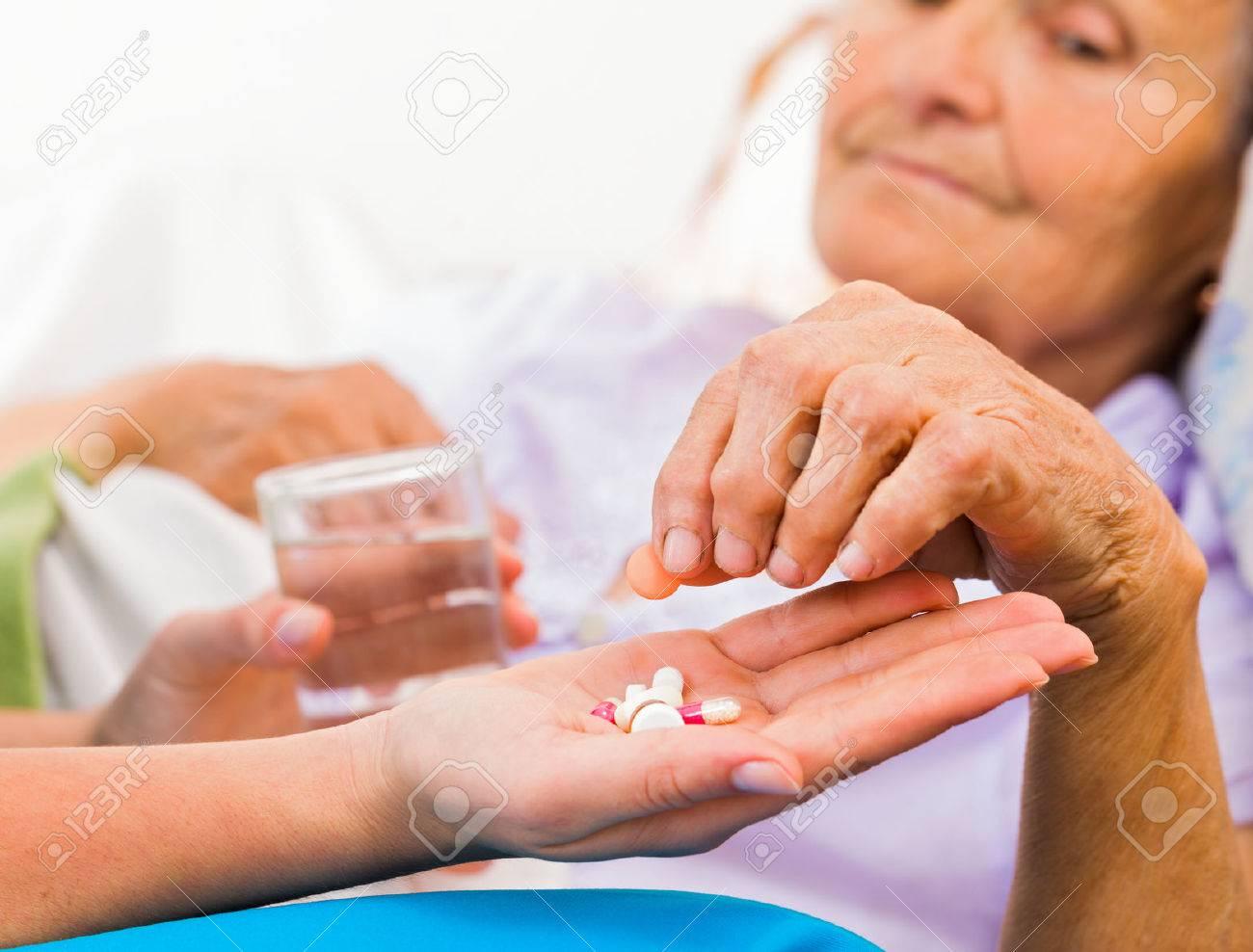 Homecare nurse helping elderly lady to take her daily medicine. Stock Photo - 55422471