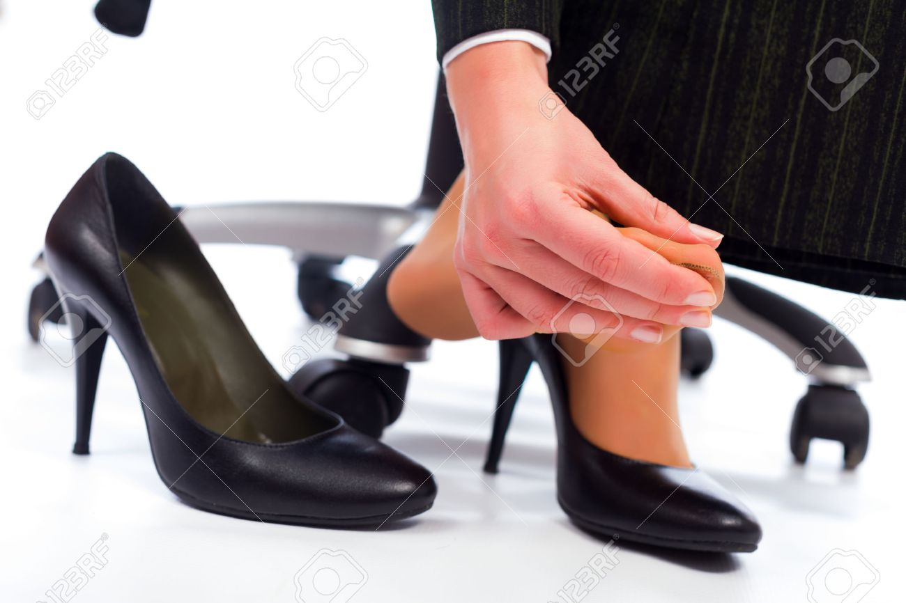 Wearing high heel shoes has its painful disadvantages - hurting feet, sole. Stock Photo - 26421120