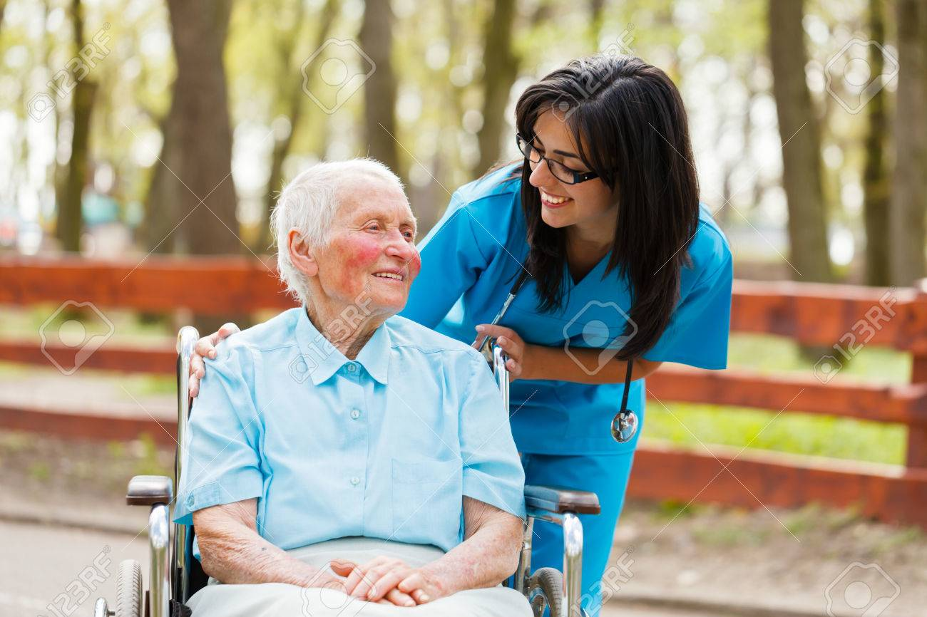 Nurse and elderly lady in wheelchair chatting outdoors. Stock Photo - 31324865