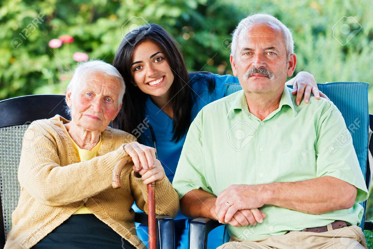 Young nurse or doctor with an elderly woman and a relative of her in the garden of the nursing home. Stock Photo - 28965447