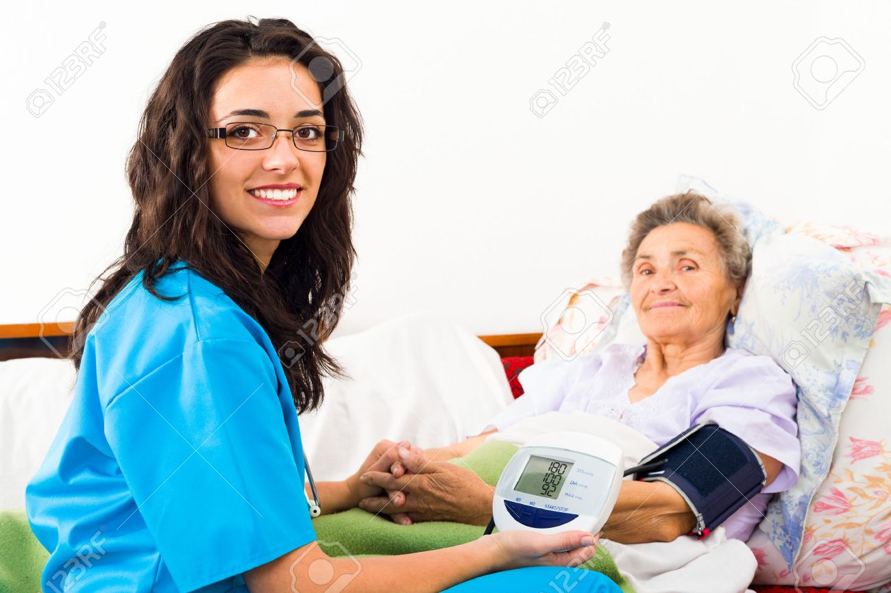 Kind nurse measuring elderly patient's blood pressure at home. Stock Photo - 42099903