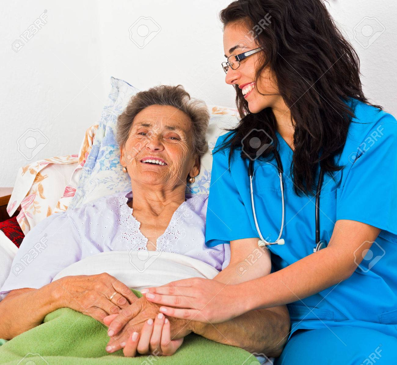 Kind nurse easing elderly lady's days in nursing home with care help and joy. Stock Photo - 42100065