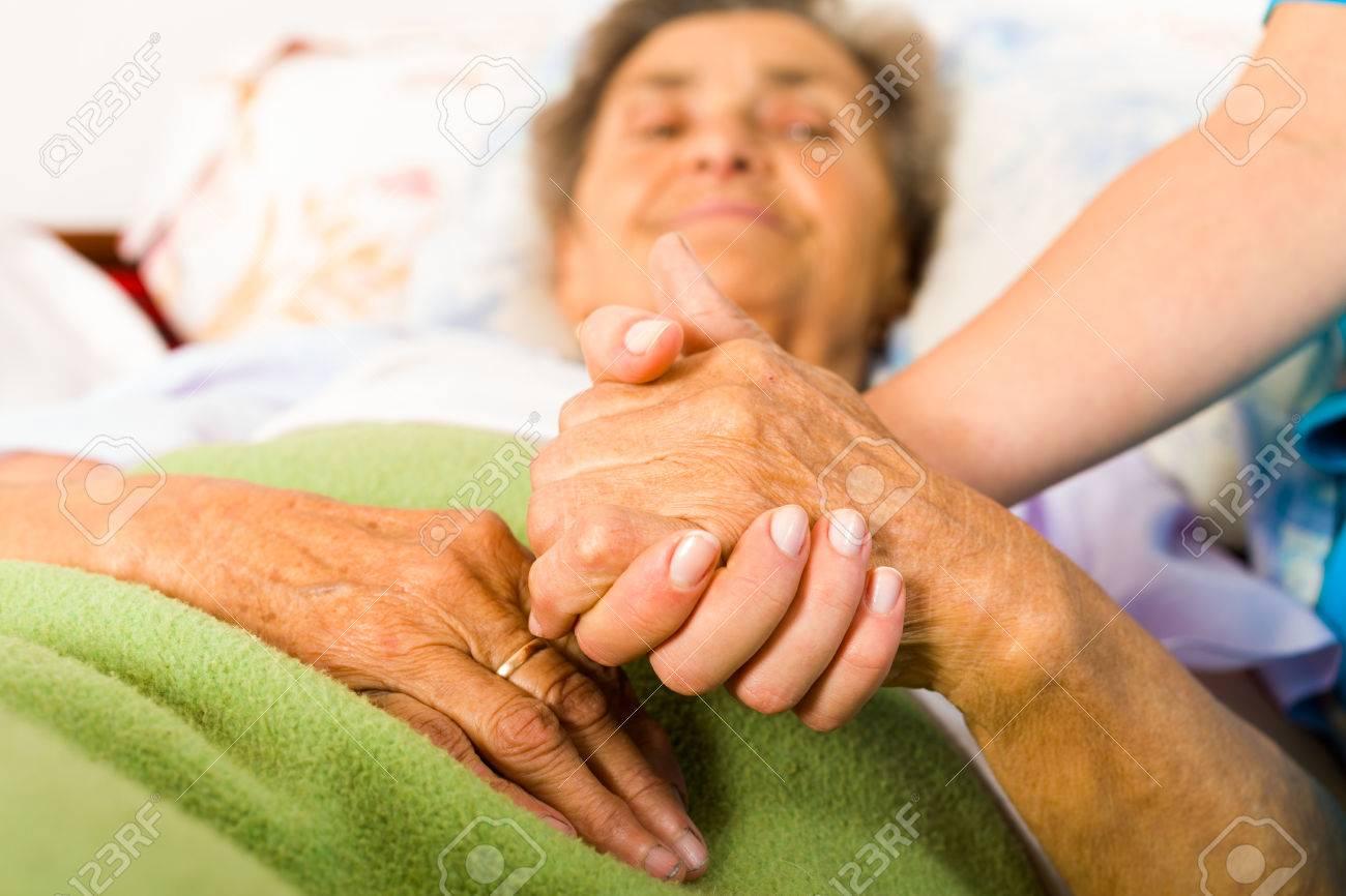 Health care nurse holding elderly lady's hand with caring attitude. Stock Photo - 42100086