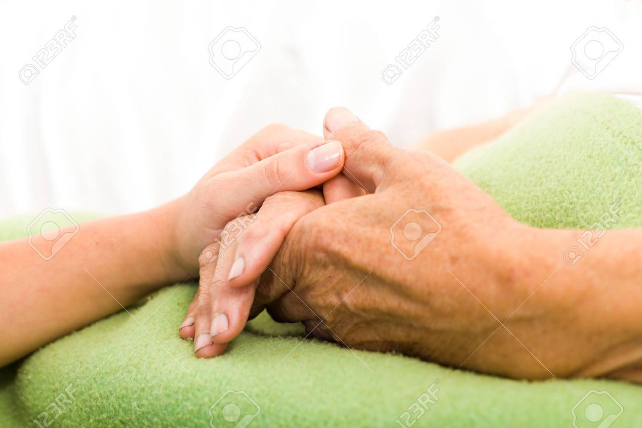 Health care nurse caring for elderly concept - holding hands. Stock Photo - 41761216