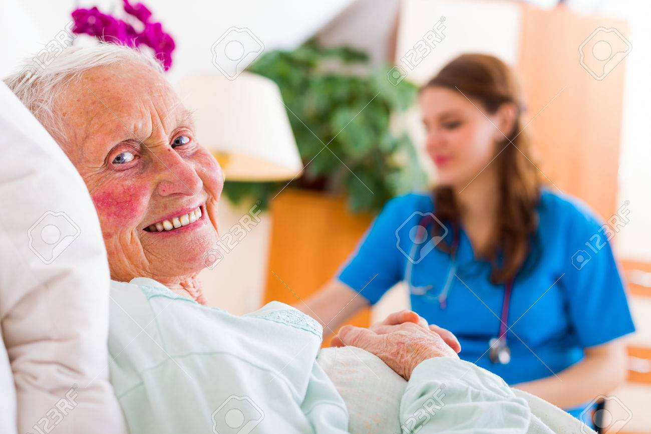 Happy senior woman laying in bed in a well equipped luxury nursing