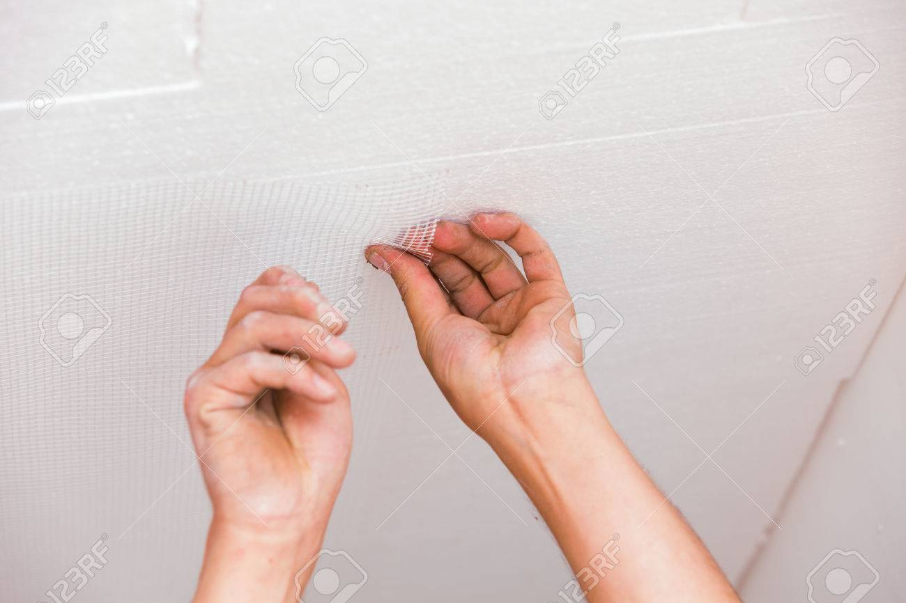 construction worker aplying glass fiber net to ceiling before
