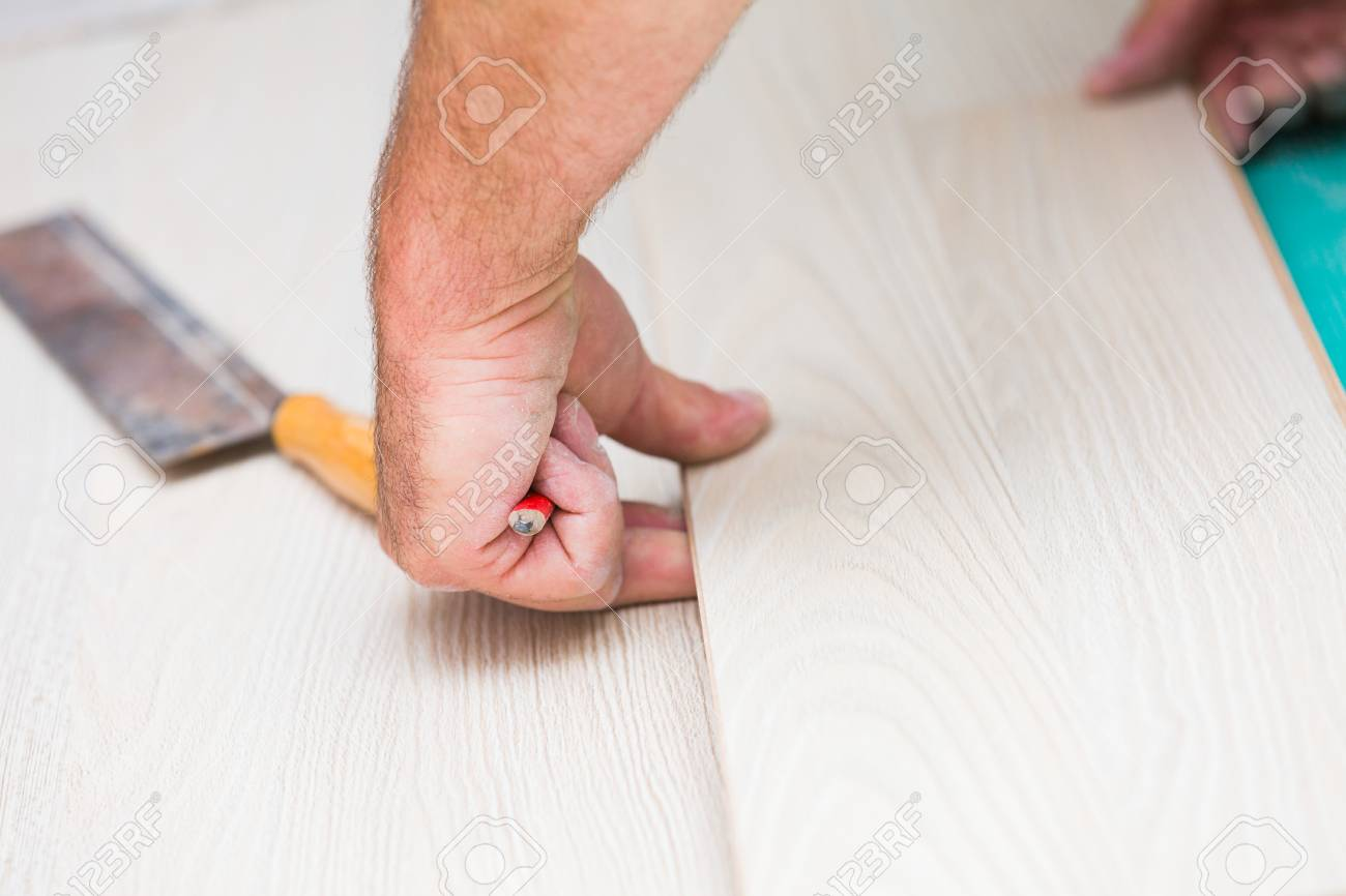 Handyman S Dusty Hands Laying Down Laminate Wood Flooring Boards