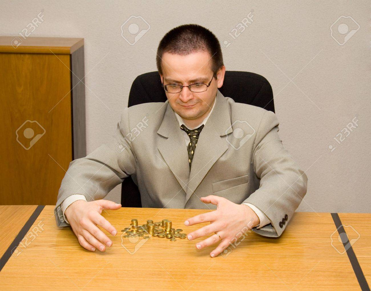Man grabbing a pile of golden coins - concept for greed, bonus Stock Photo - 885589
