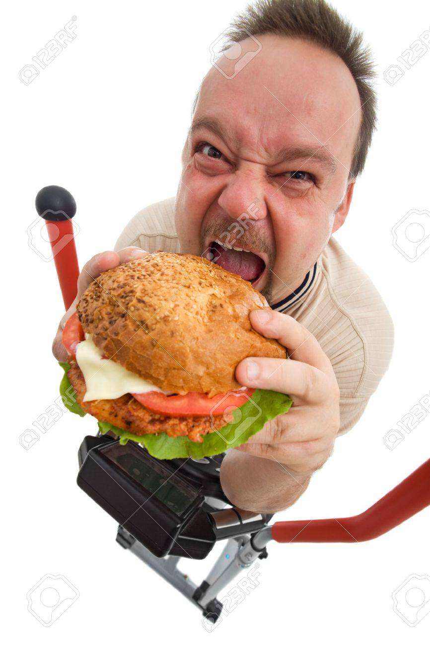To hell with exercises - man eating big hamburger on elliptical trainer device - isolated Stock Photo - 8054980
