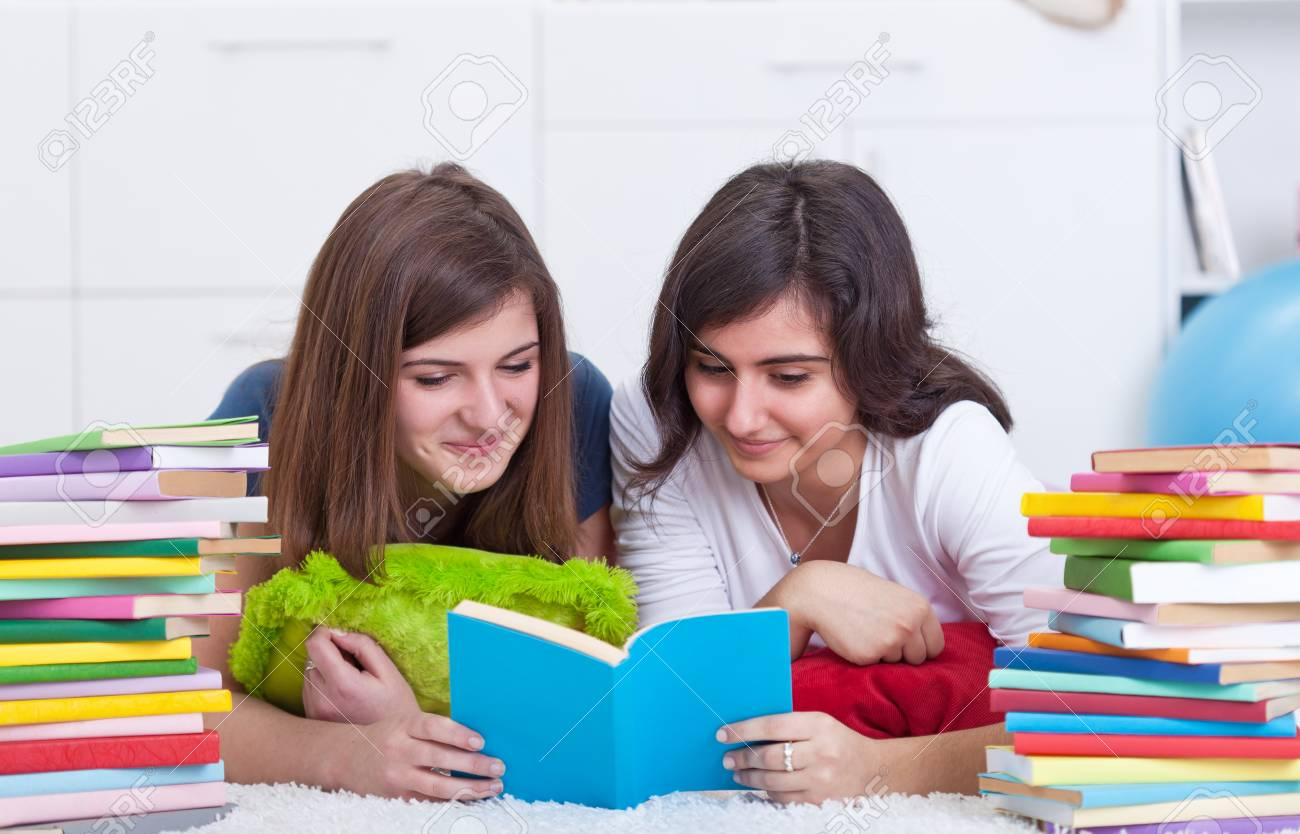 Teenager girls with lots of books study and read together Stock Photo - 12148272
